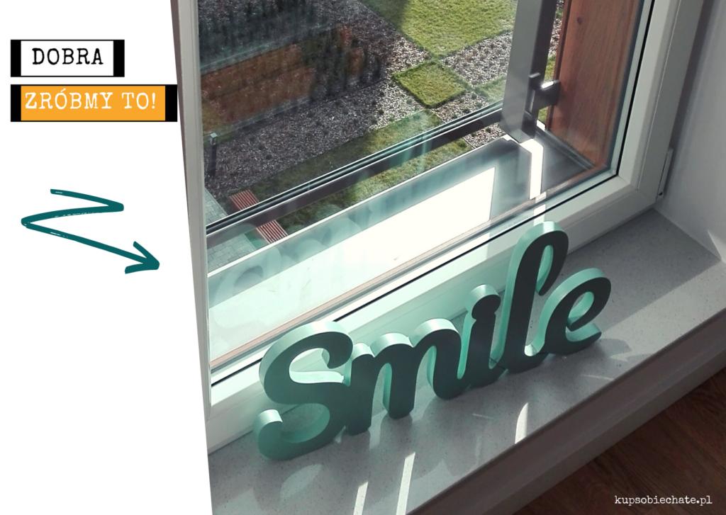 napis smile na oknie i wdok kwietnika w dole za oknem. Nasz pierwszy samodzielny projekt.